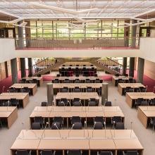 Zeigt einen Hörsaal von außen und Studenten die davor stehen
