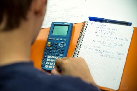 Zeigt einen Schreibblock auf einem Tisch sowie eine Person, die einen Taschenrechner bedient