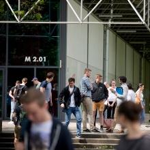 Dieses Bild zeigt Zeigt einen Hörsaal von außen und Studenten die davor stehen
